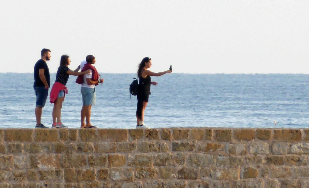Taking selfies on the wall of the harbour front